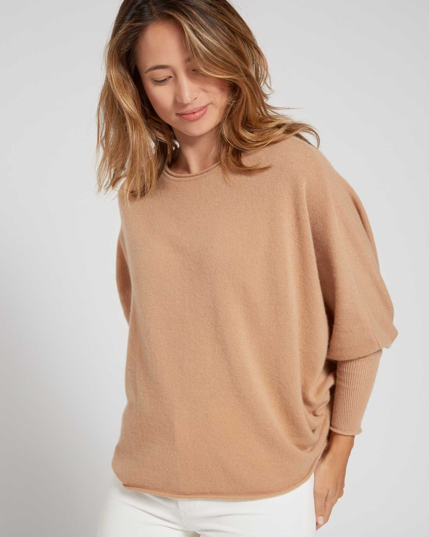 Woman wearing batwing sweater made from cashmere in camel