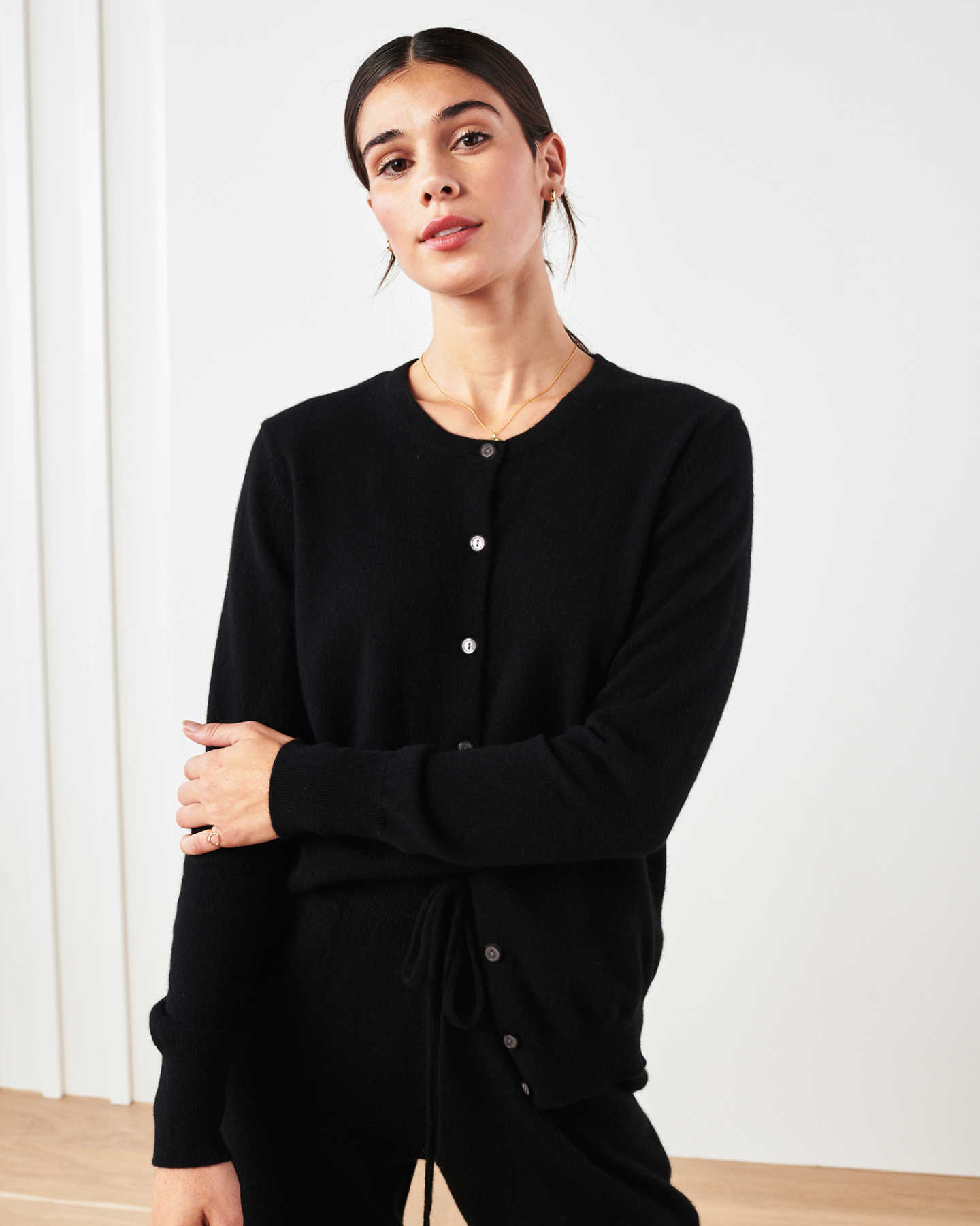 Woman wearing black cashmere cardigan sweater and black cashmere sweatpants smiling