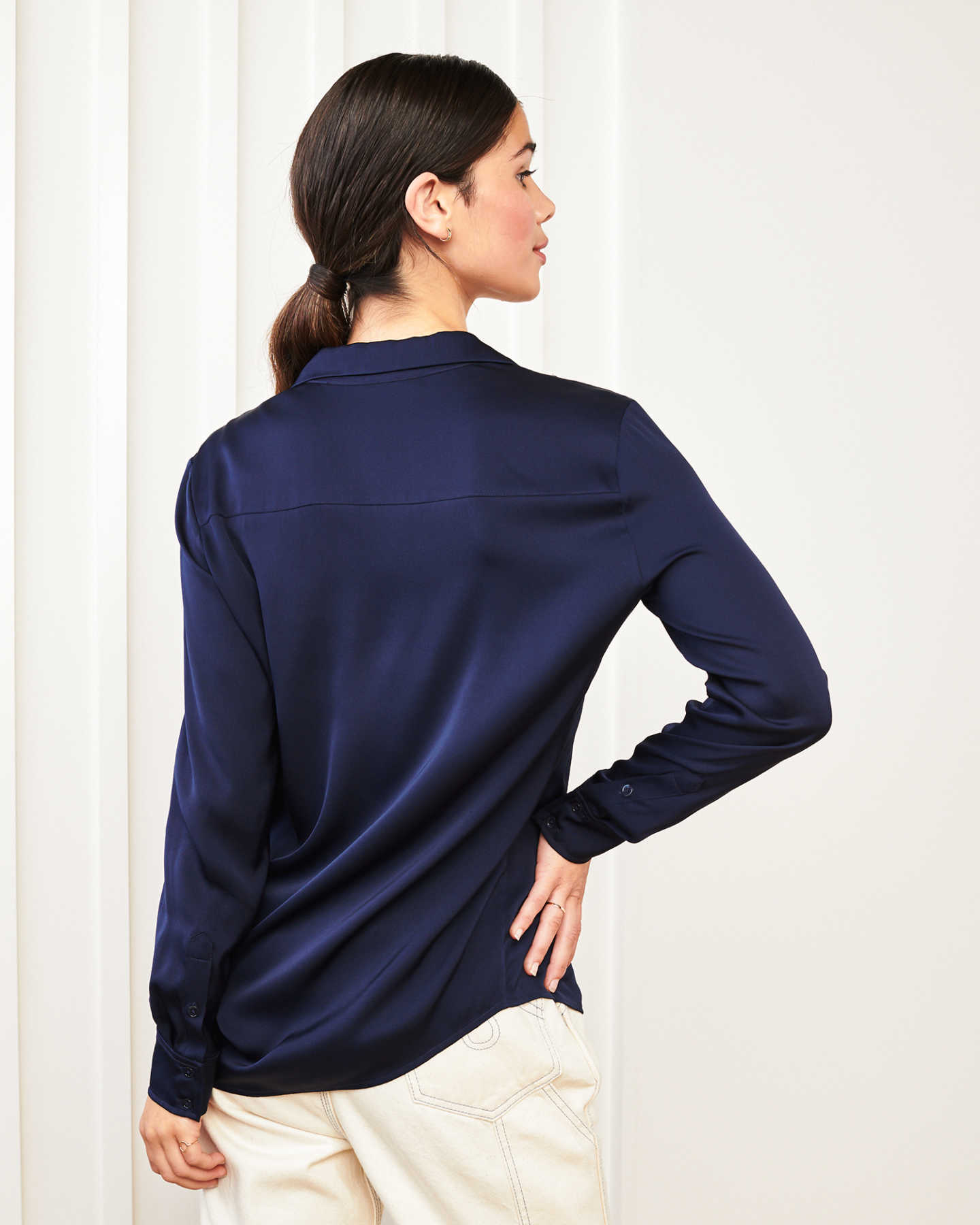 woman wearing silk notch collar blouse in navy with hand on hip