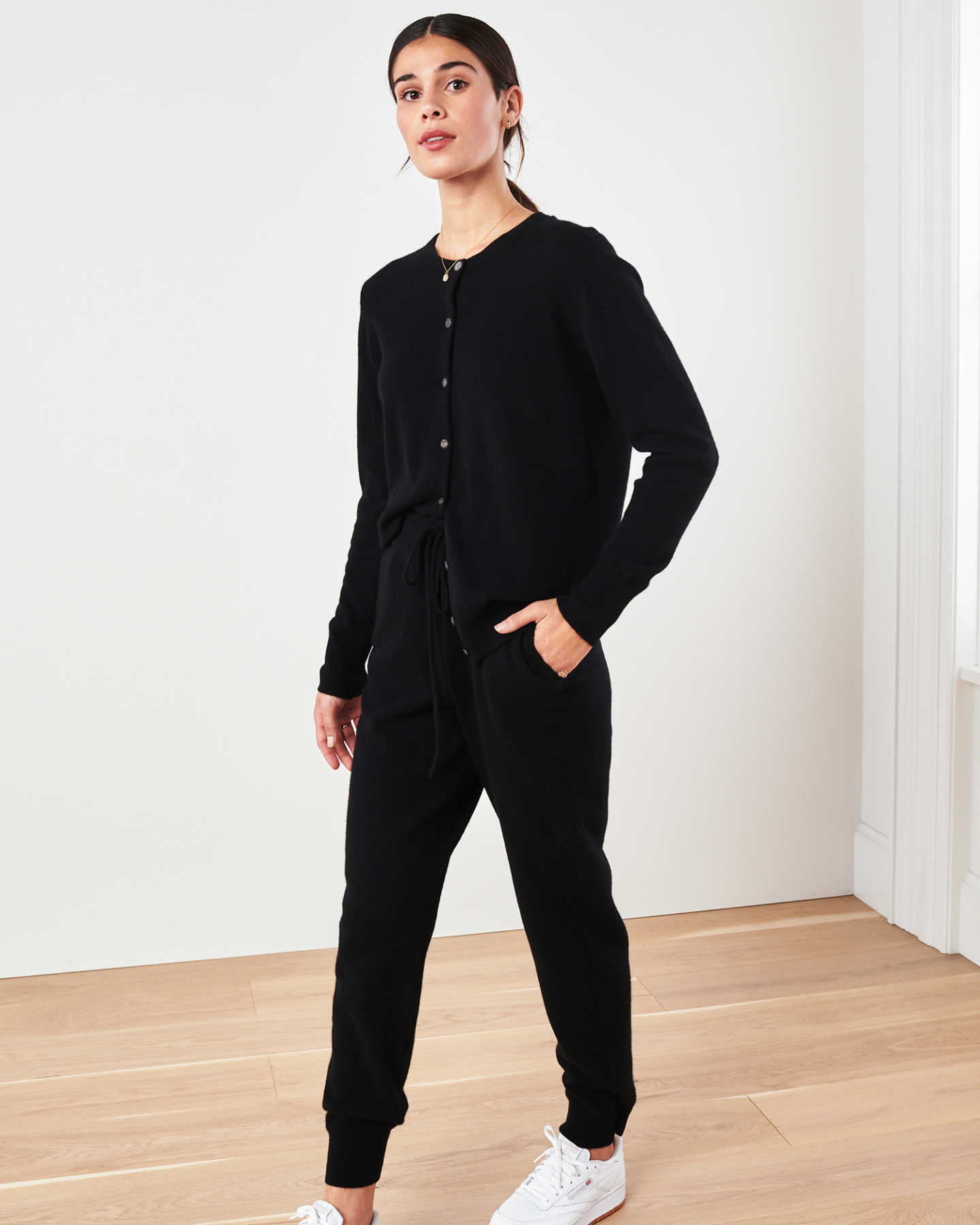 Woman wearing black cashmere cardigan sweater and black cashmere sweatpants walking