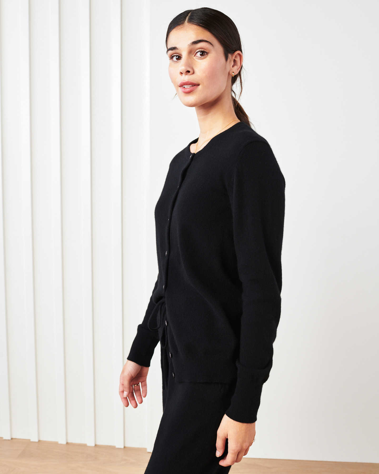 Woman wearing black cashmere cardigan sweater and black cashmere sweatpants thinking
