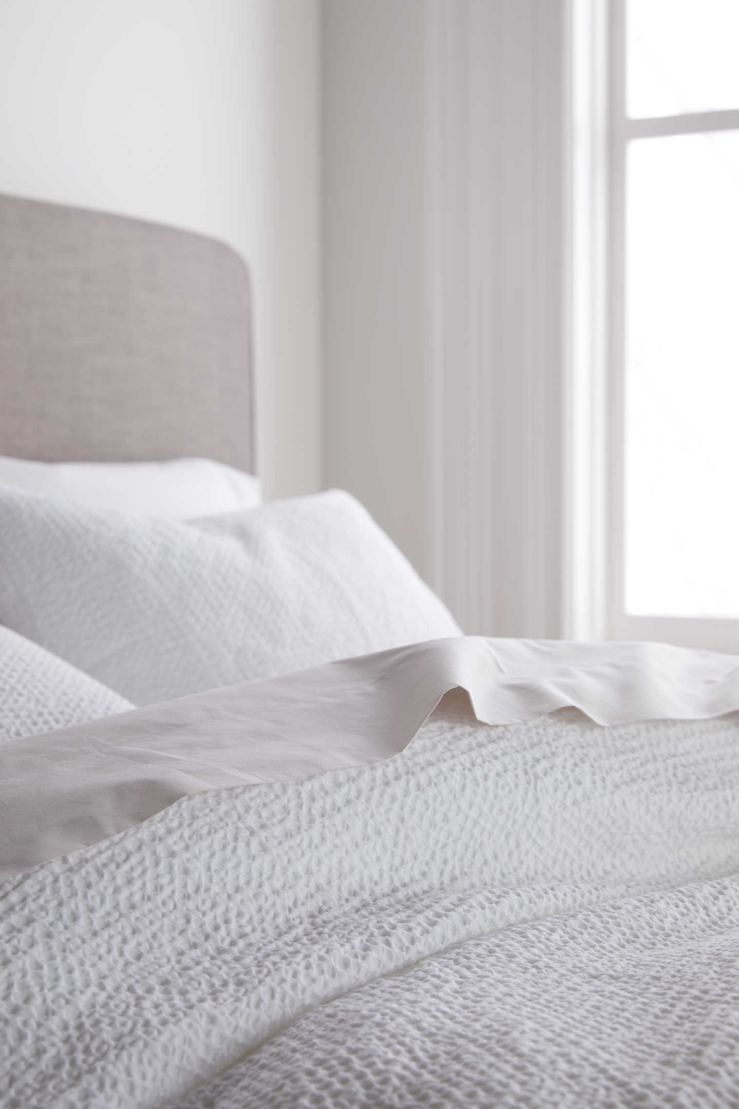 waffle duvet cover on bed from angle in white