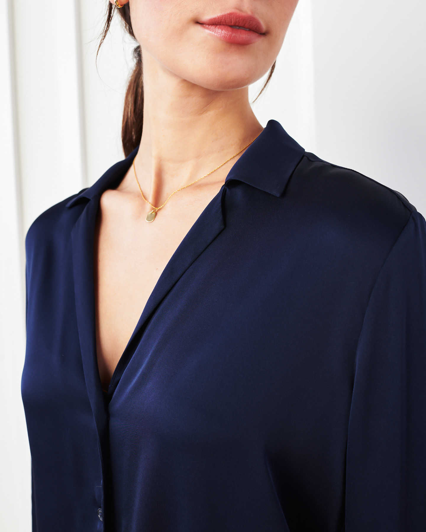 woman wearing silk notch collar blouse in navy zoomed in
