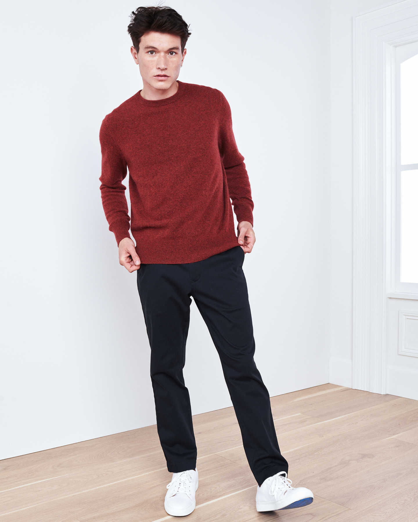 Man wearing red men's cashmere sweater by window