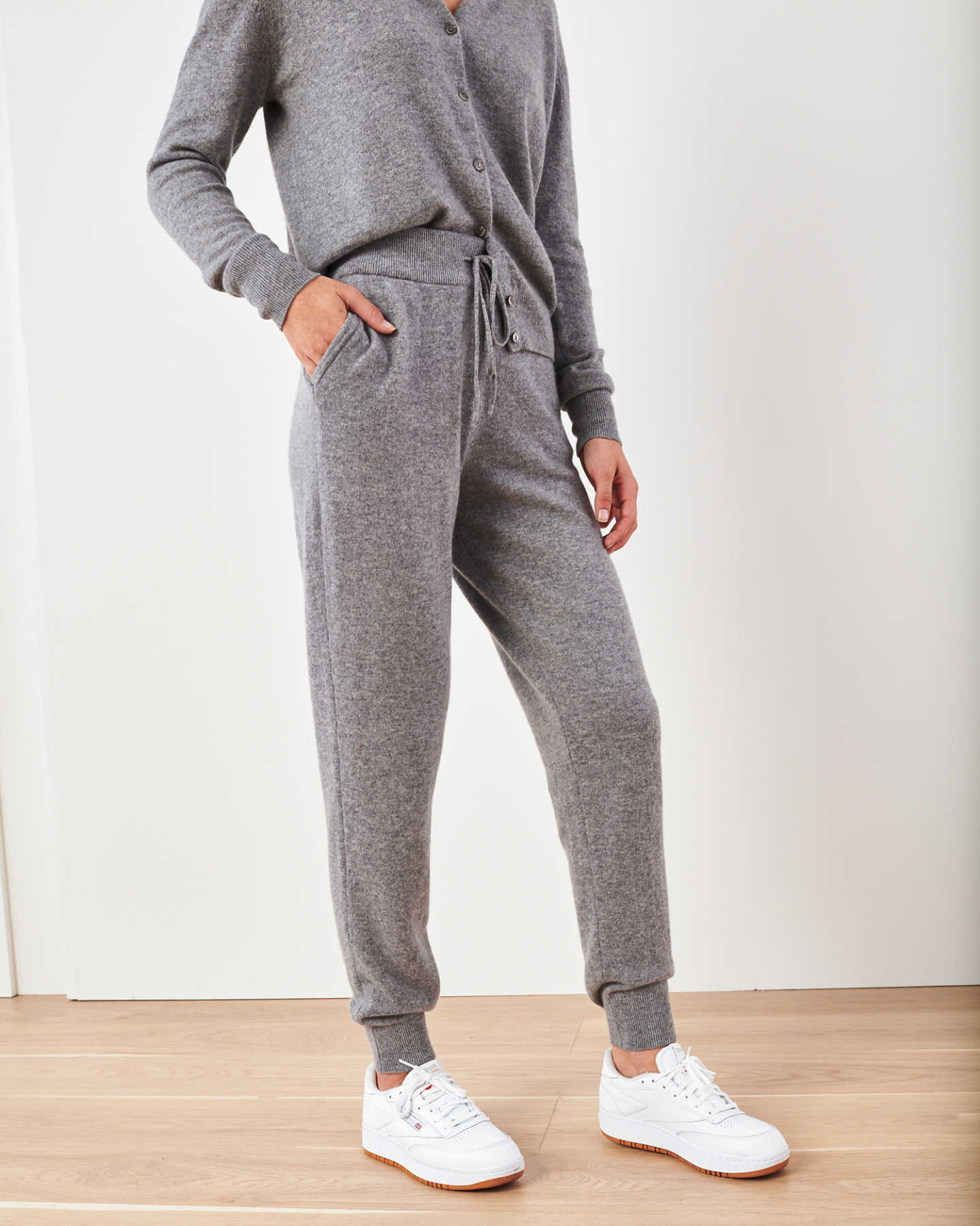 Woman wearing grey cashmere sweatpants & cashmere joggers standing