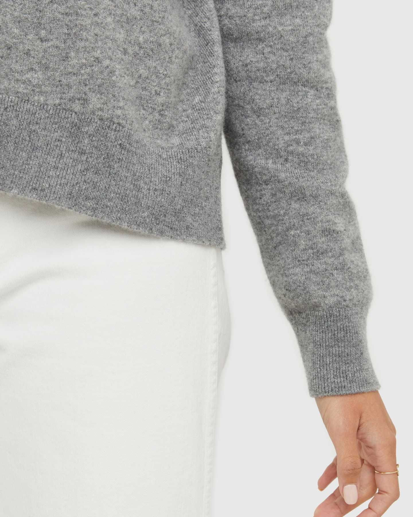 Woman wearing grey cashmere mockneck sweater zoomed in on sleeve