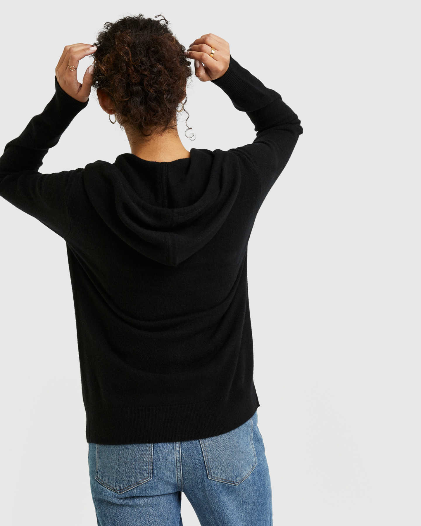 Woman wearing black cashmere zip hoodie from back