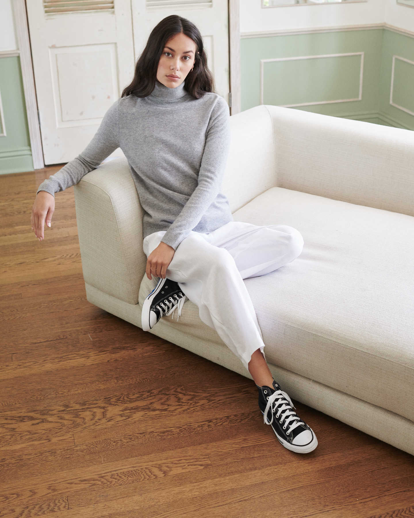 Woman wearing grey cashmere turtleneck sweater on couch