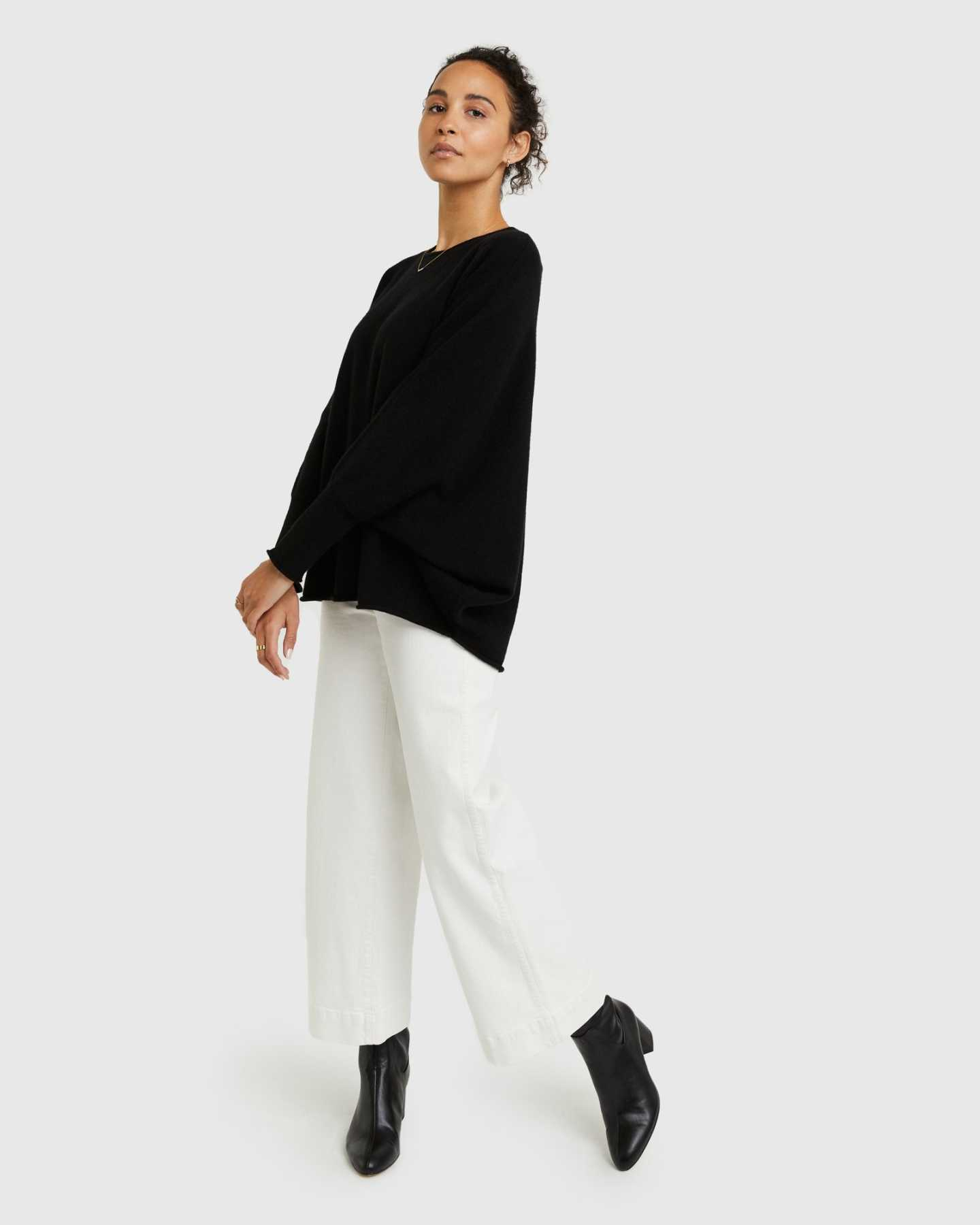 Woman wearing batwing sweater made from cashmere in black from the side