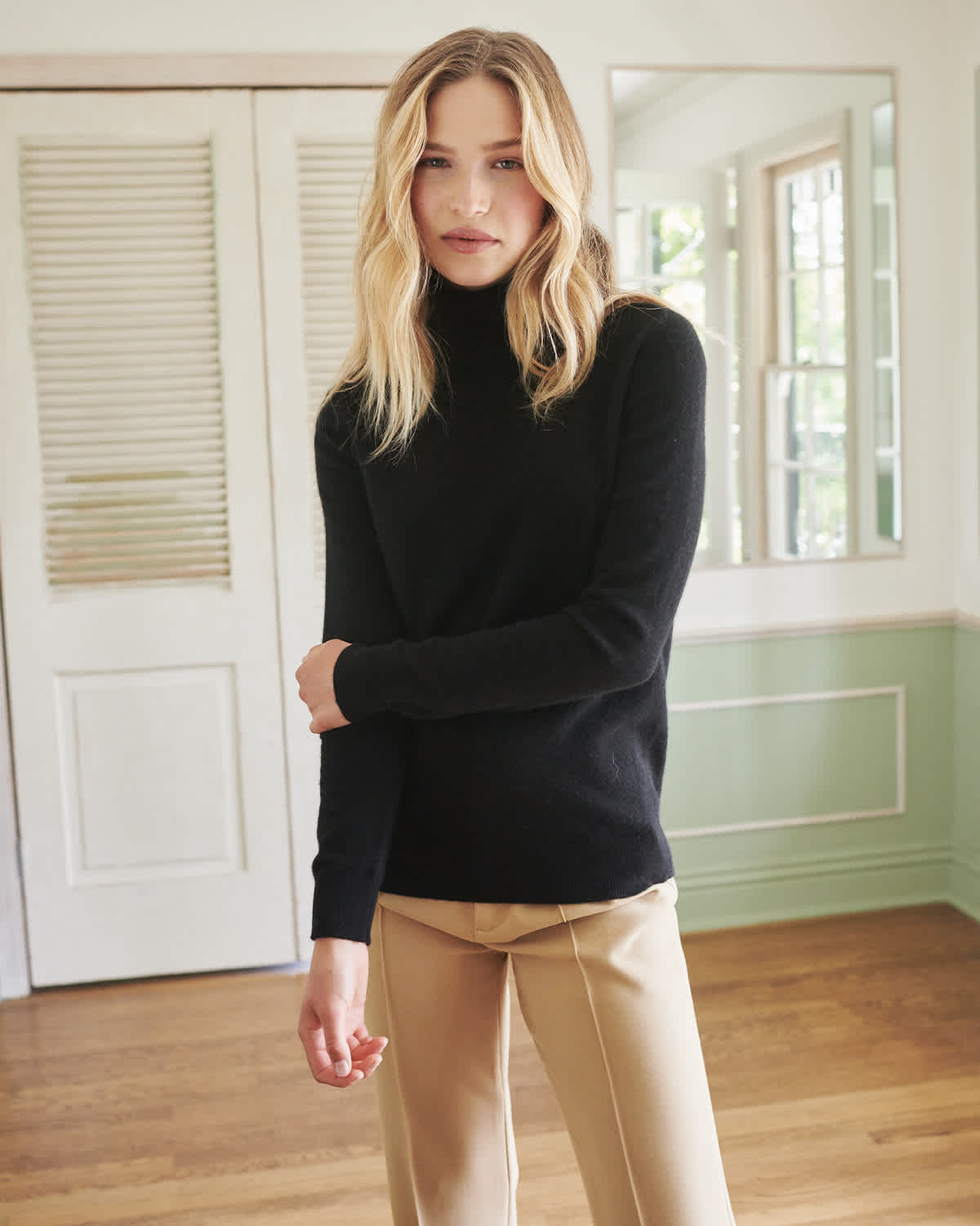 Woman wearing black cashmere turtleneck sweater close