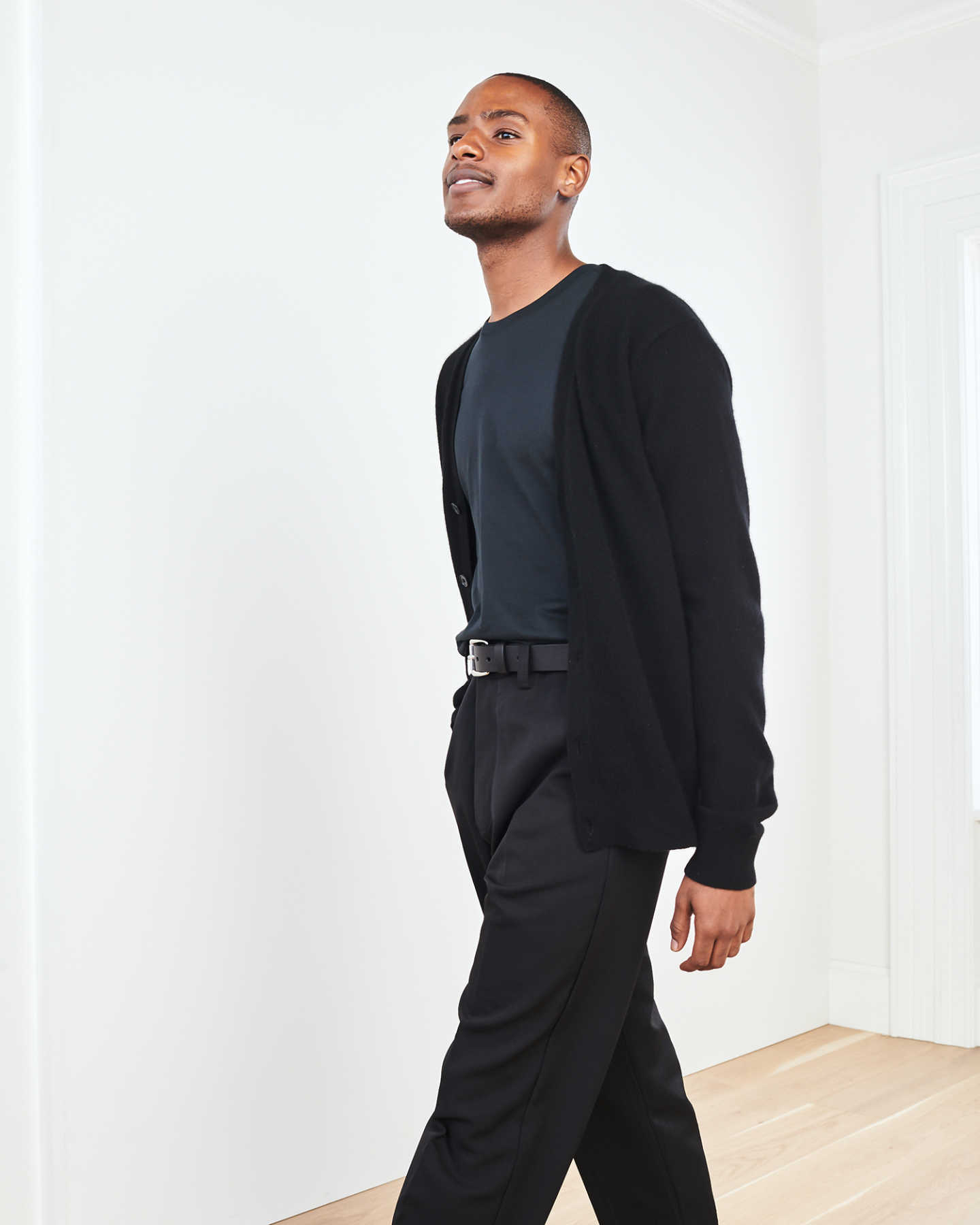Men's cashmere cardigan sweater in black by wall
