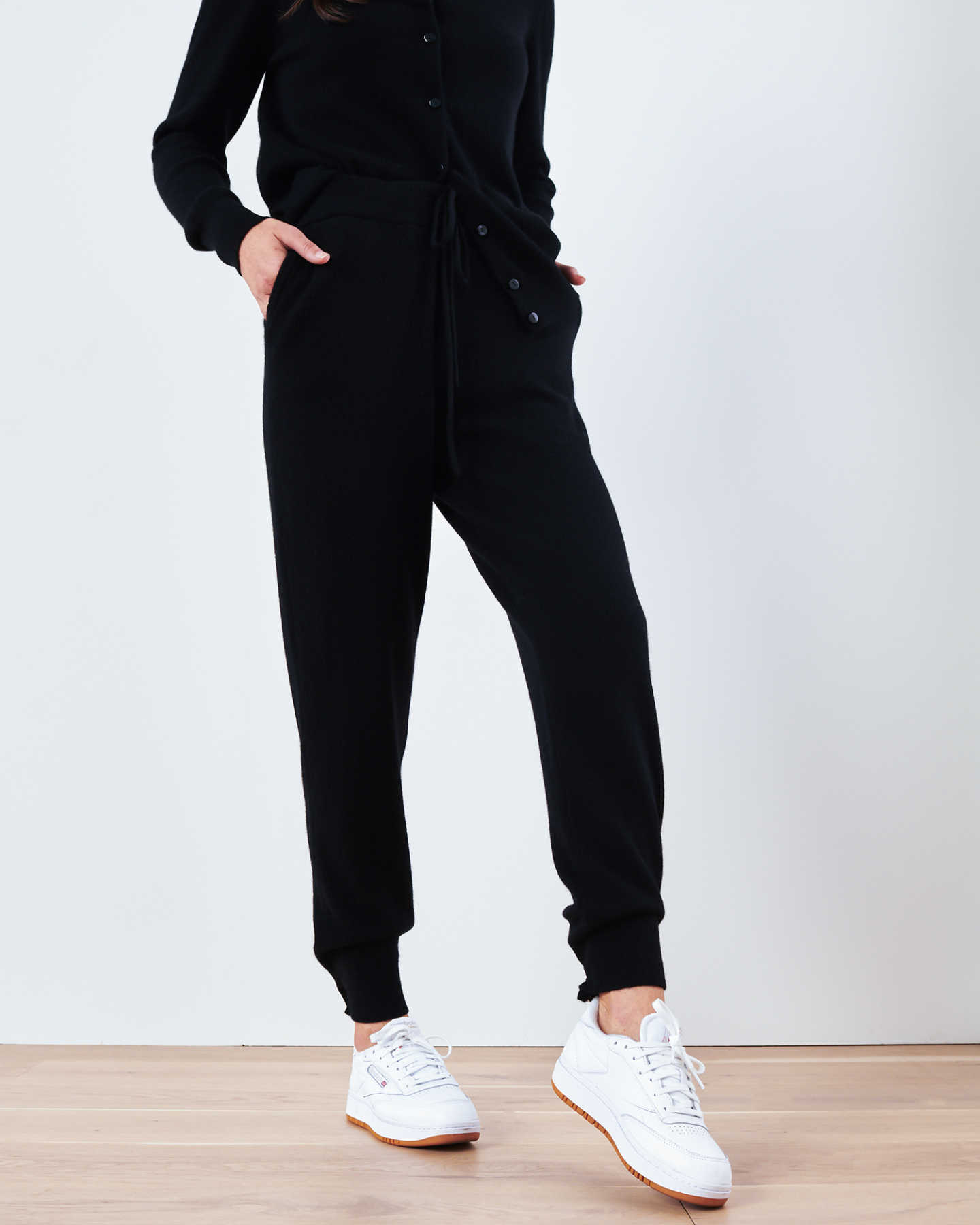 Woman wearing black cashmere sweatpants & cashmere joggers with white sneakers