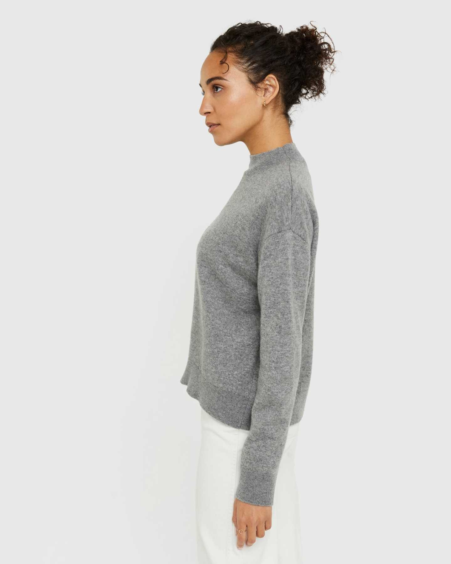 Woman wearing grey cashmere mockneck sweater from side looking away