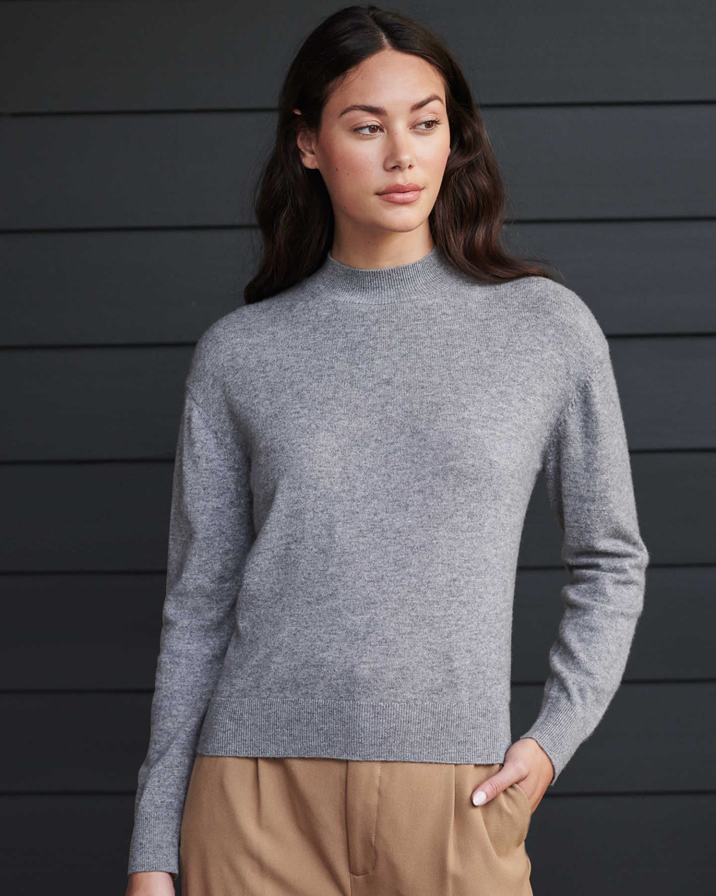 Woman wearing grey cashmere mockneck sweater looking to the side