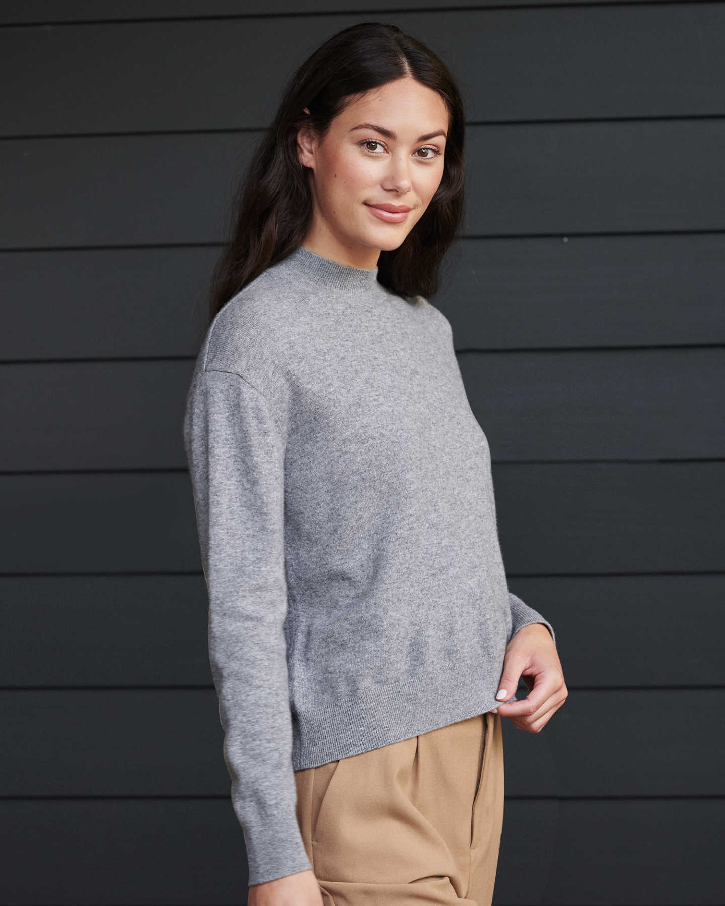 Woman wearing grey cashmere mockneck sweater smiling at the camera