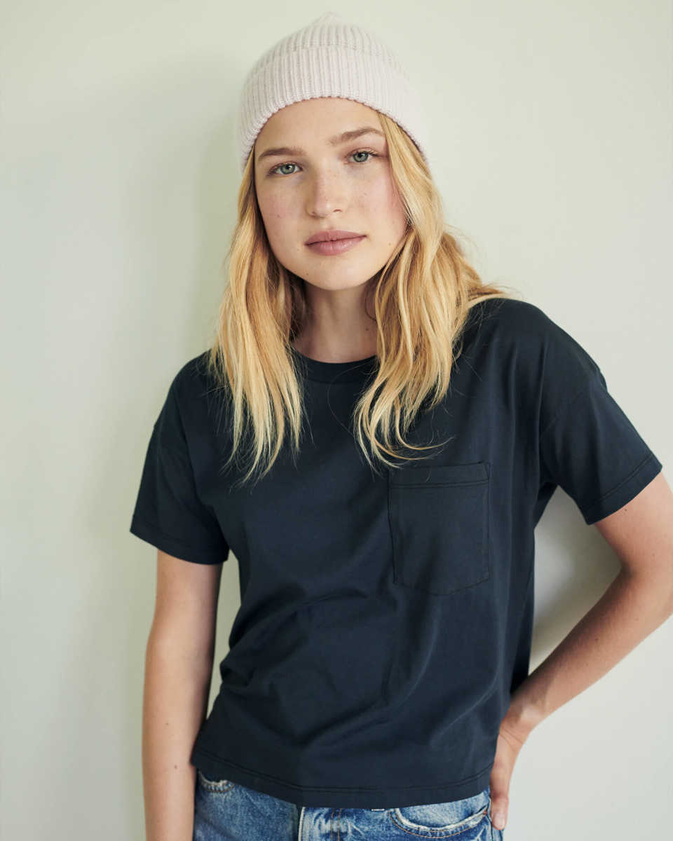 Woman wearing a blue pima tee and pink cashmere beanie