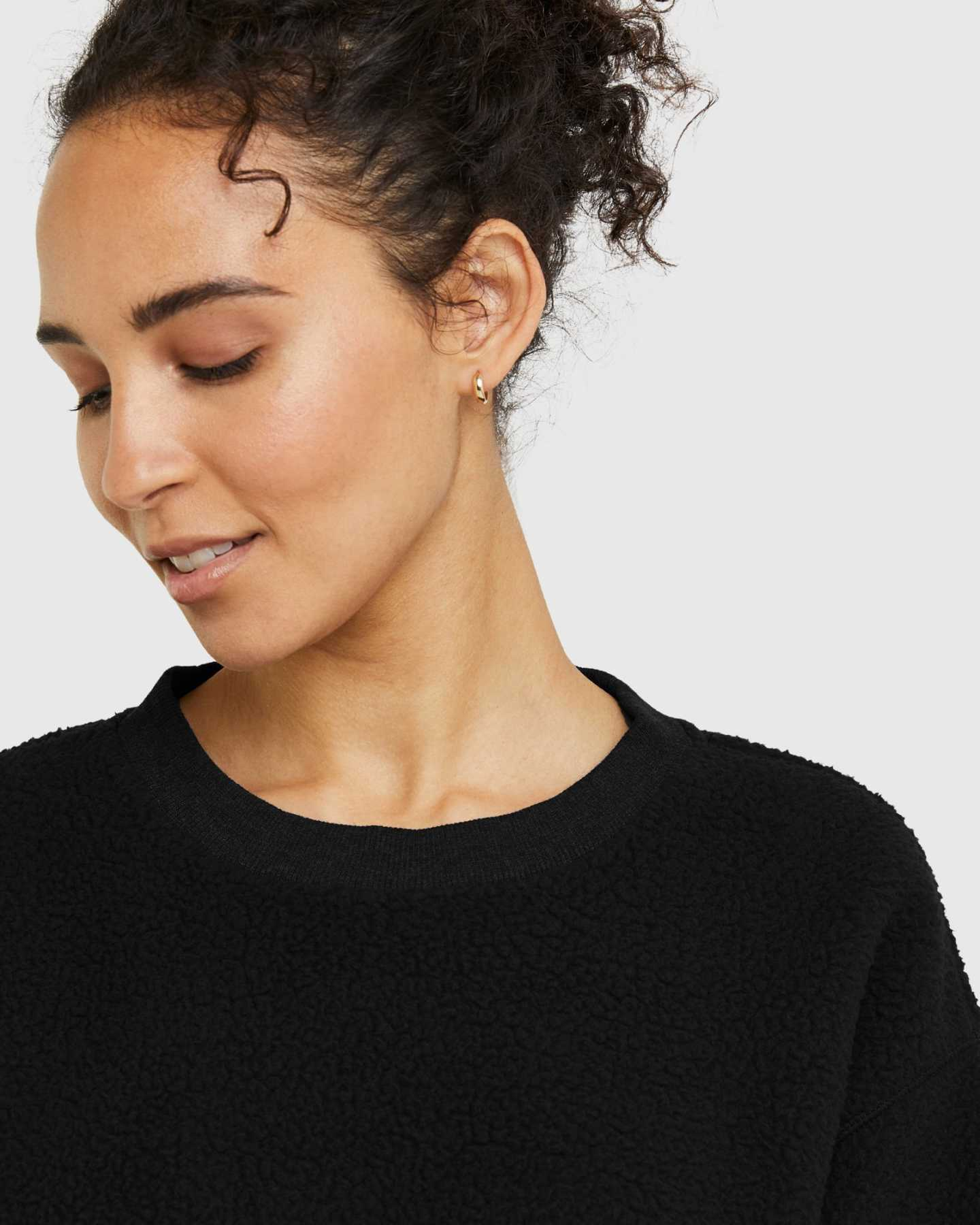 woman wearing sherpa crewneck sweatshirt in black neckline