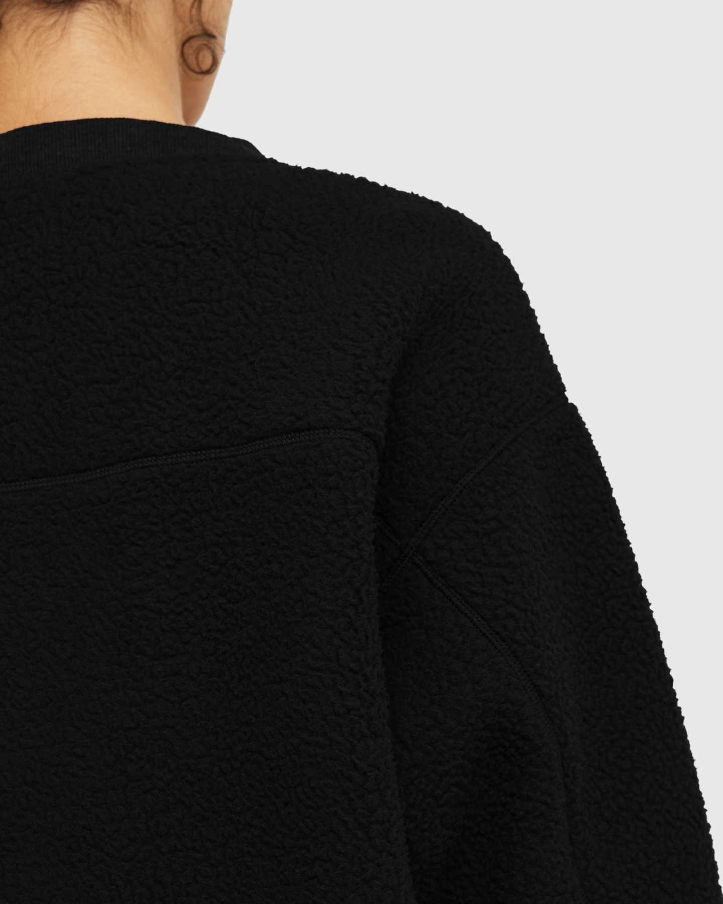 woman wearing sherpa crewneck sweatshirt in black zoomed in on shoulder