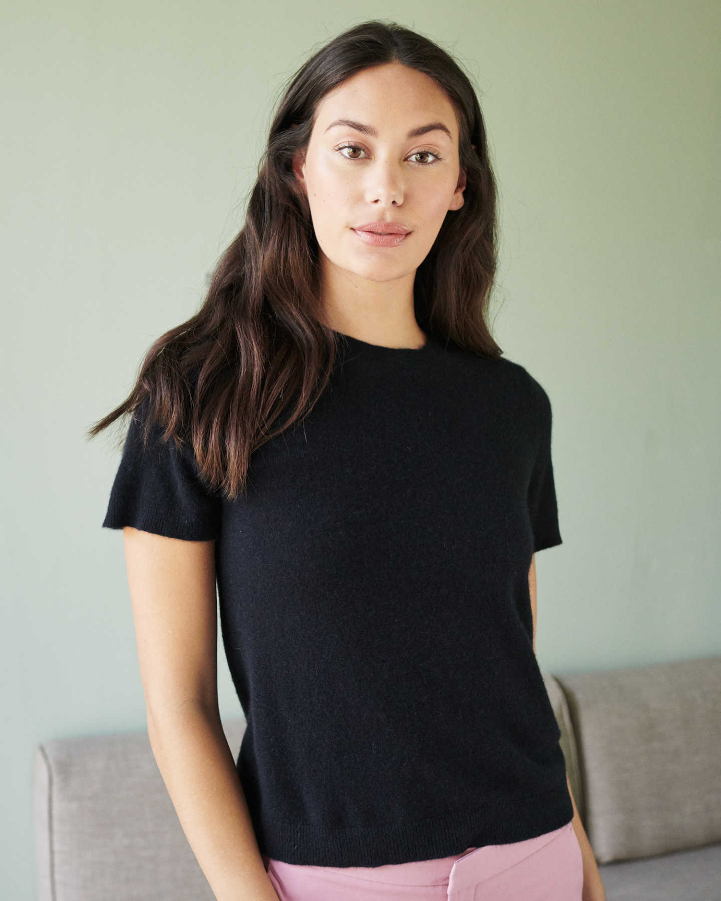woman wearing black cashmere tee looking at the camera