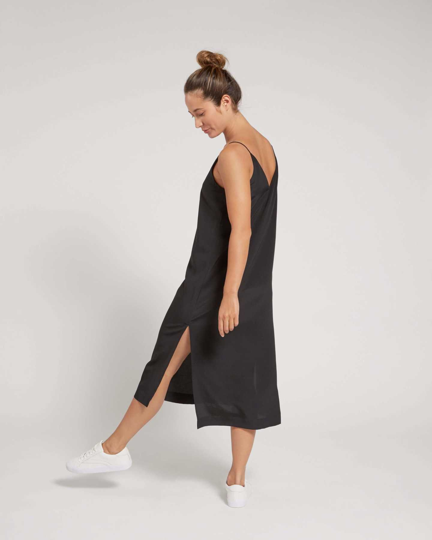 Woman wearing black silk slip dress from side