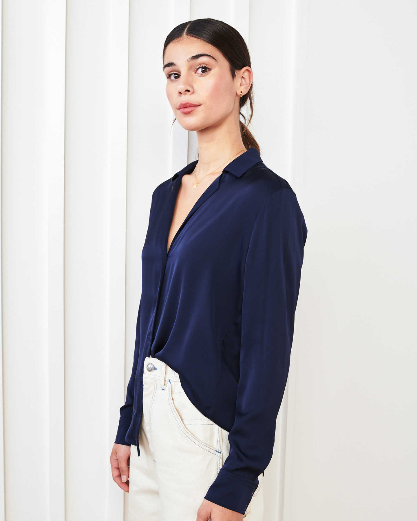 woman wearing silk notch collar blouse in navy from angle