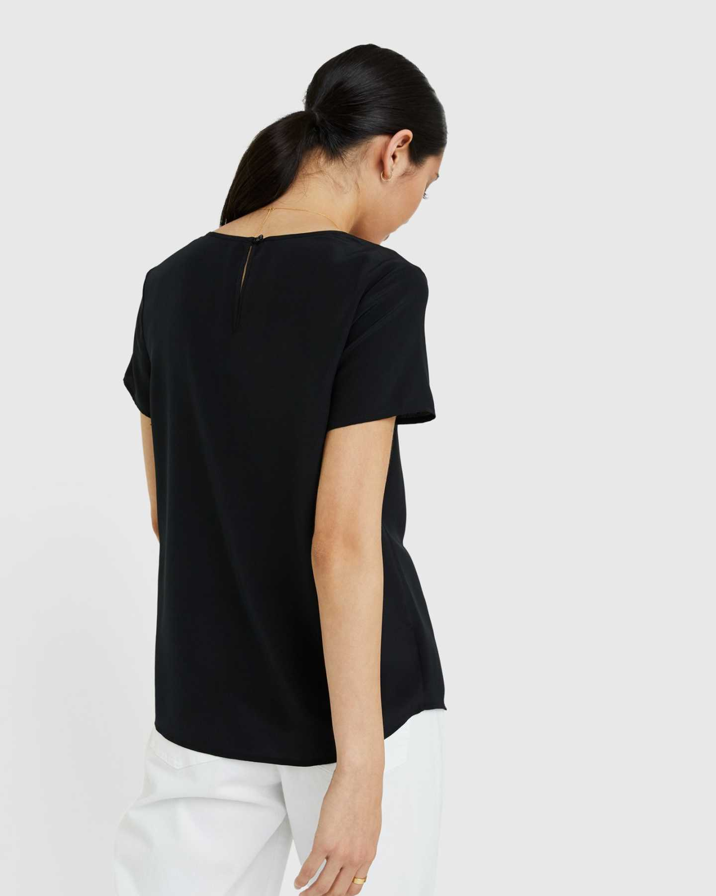 Woman wearing silk tee in black from back