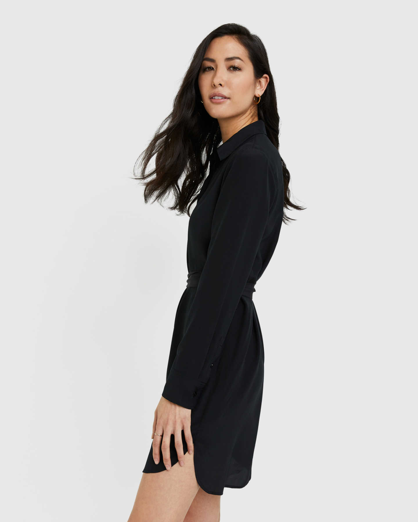 Woman wearing silk shirt dress in black from side