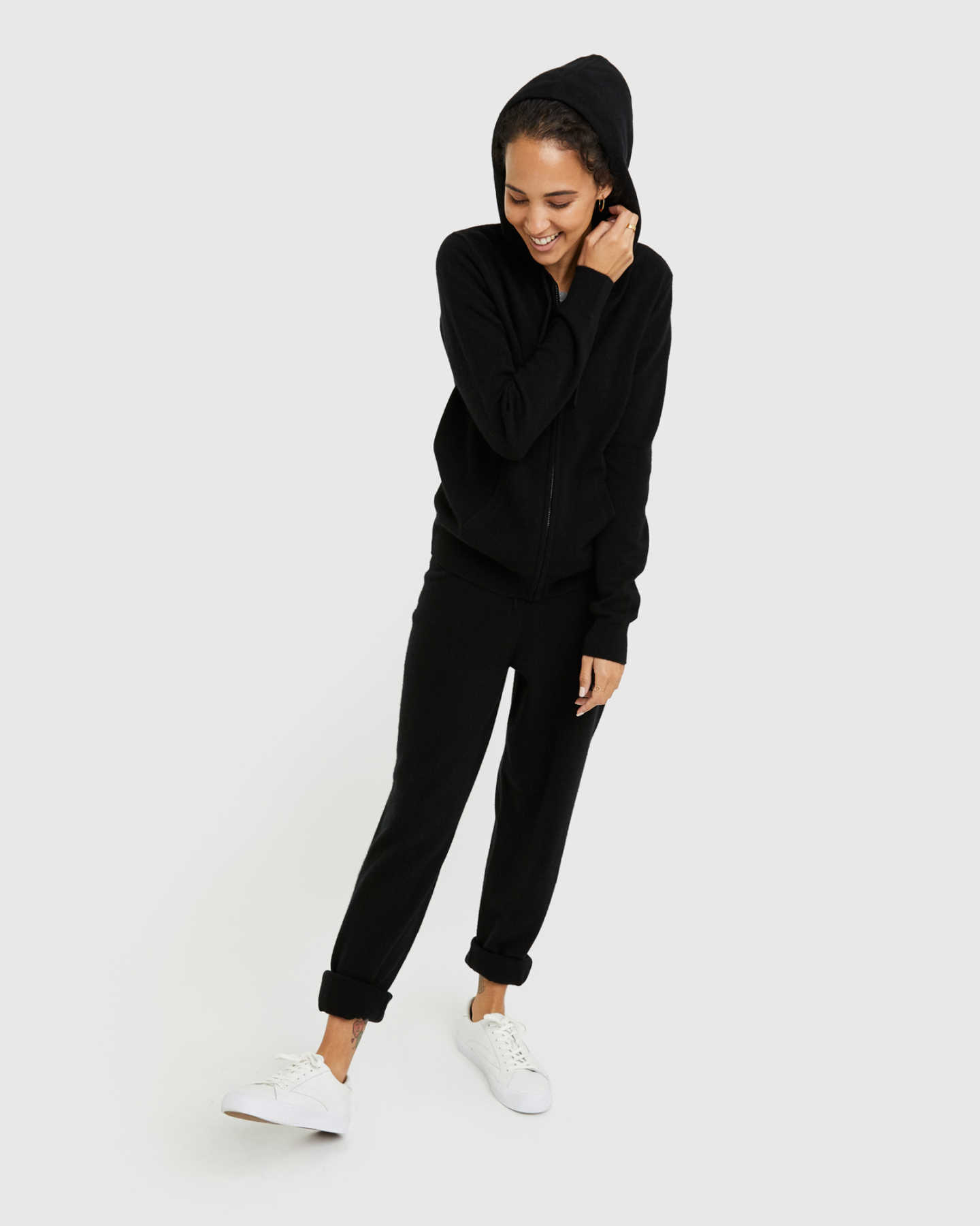 Woman wearing black cashmere zip hoodie and matching cashmere sweatpants smiling