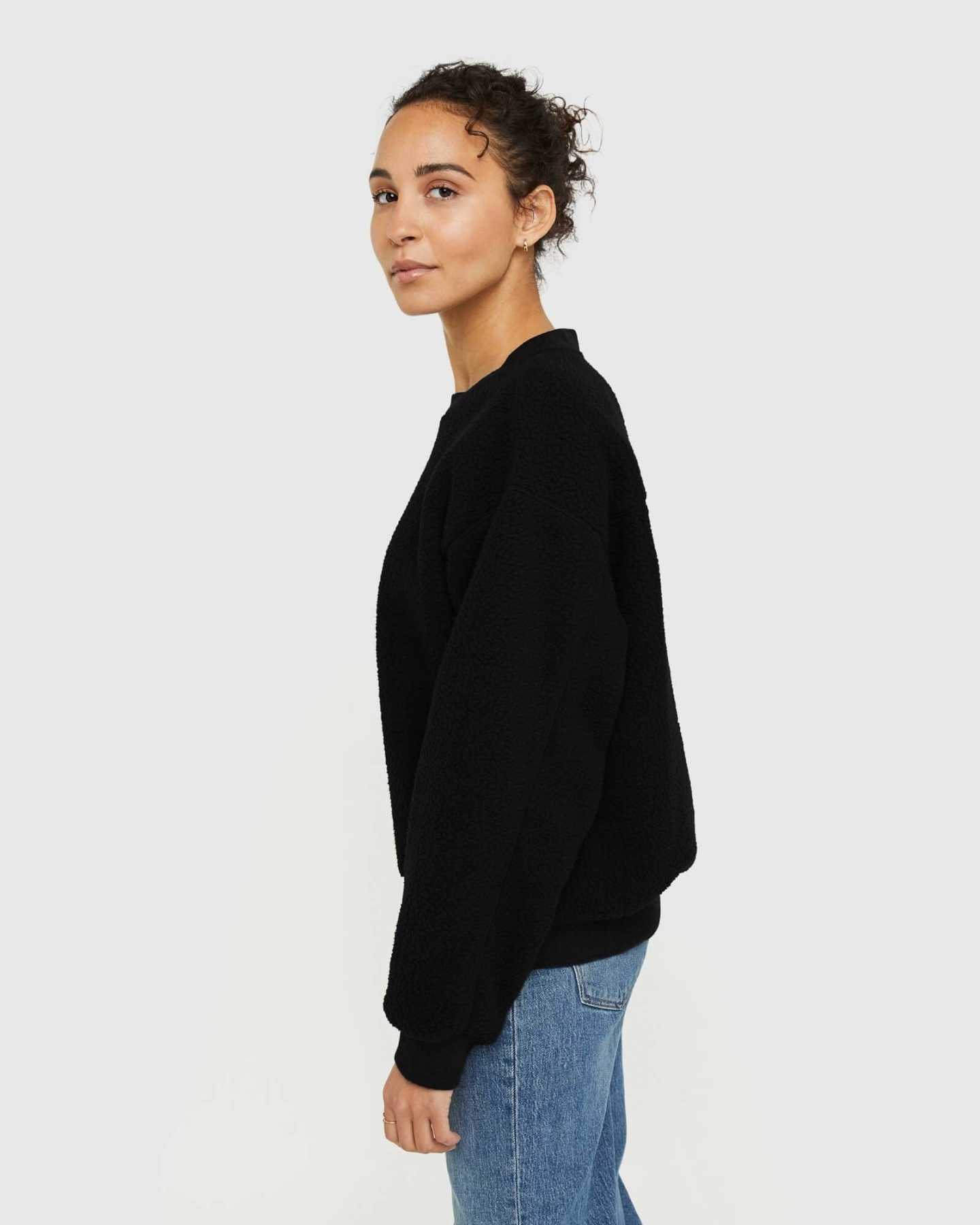 woman wearing sherpa crewneck sweatshirt in black from side
