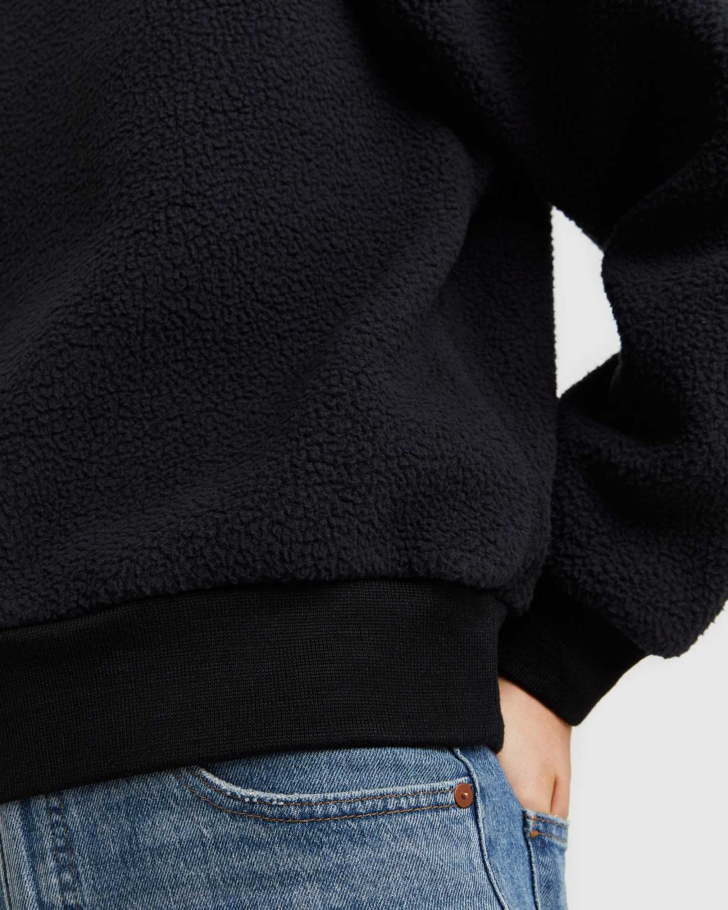 woman wearing sherpa crewneck sweatshirt in black sleeve