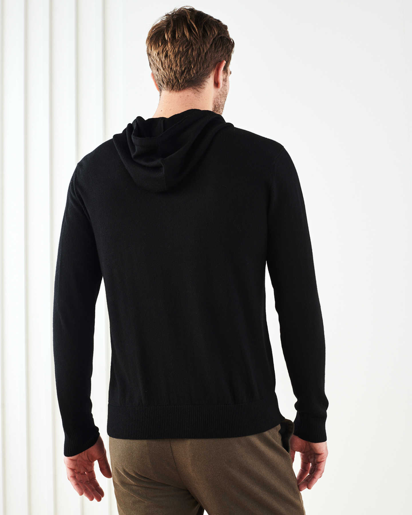 Man wearing merino wool hoodie in black from back