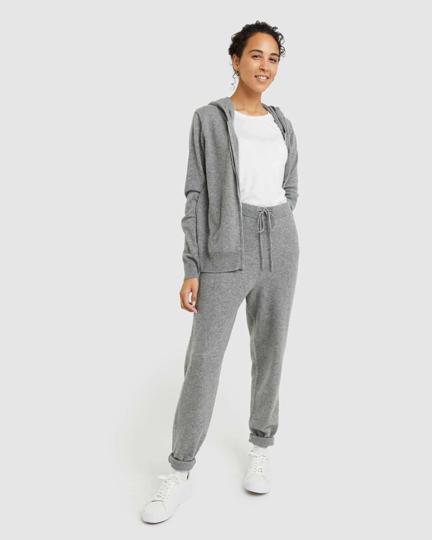 Woman wearing grey cashmere zip hoodie and matching cashmere sweatpants standing