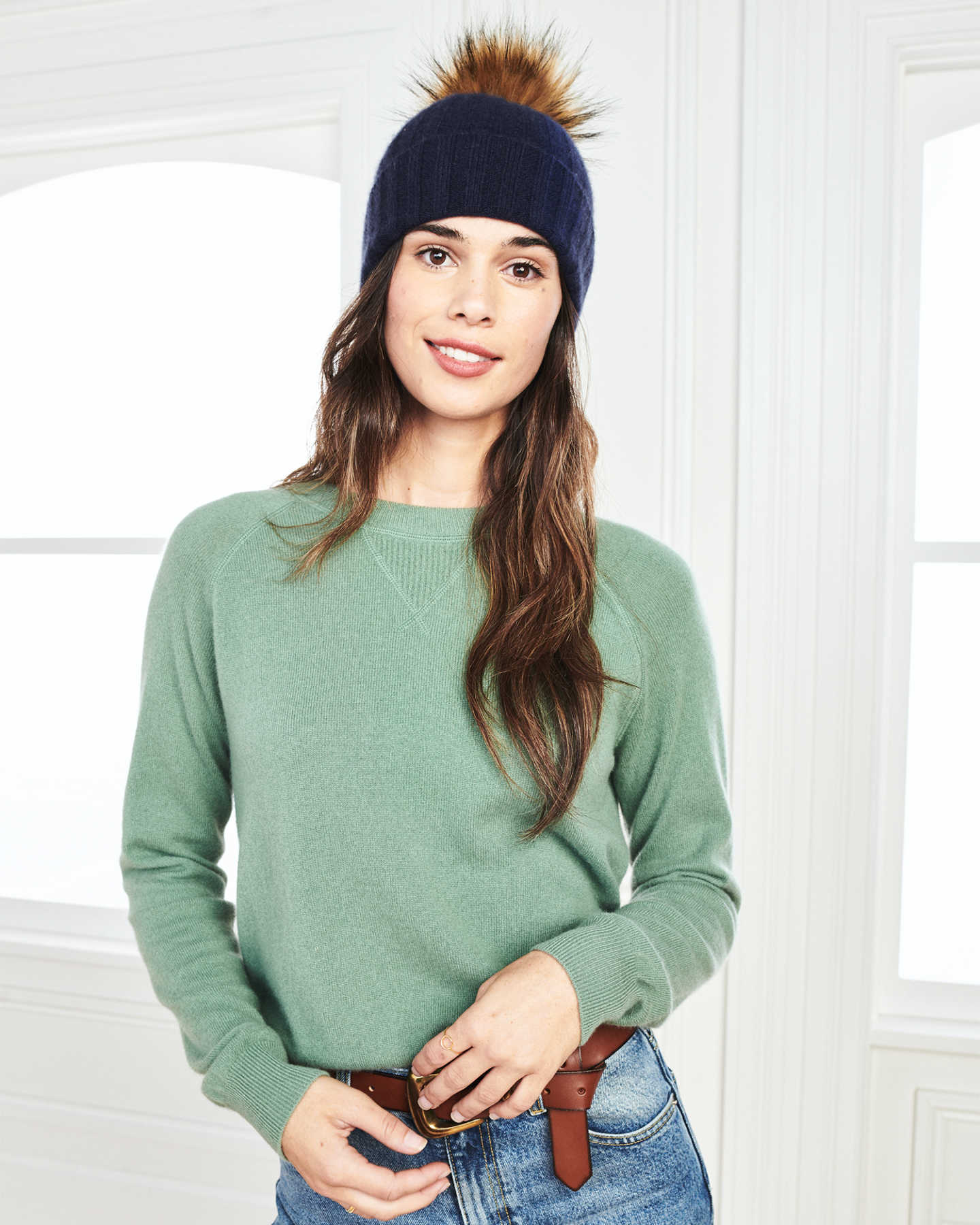Woman wearing a womens beanie with pom in navy and matching cashmere sweatshirt in green