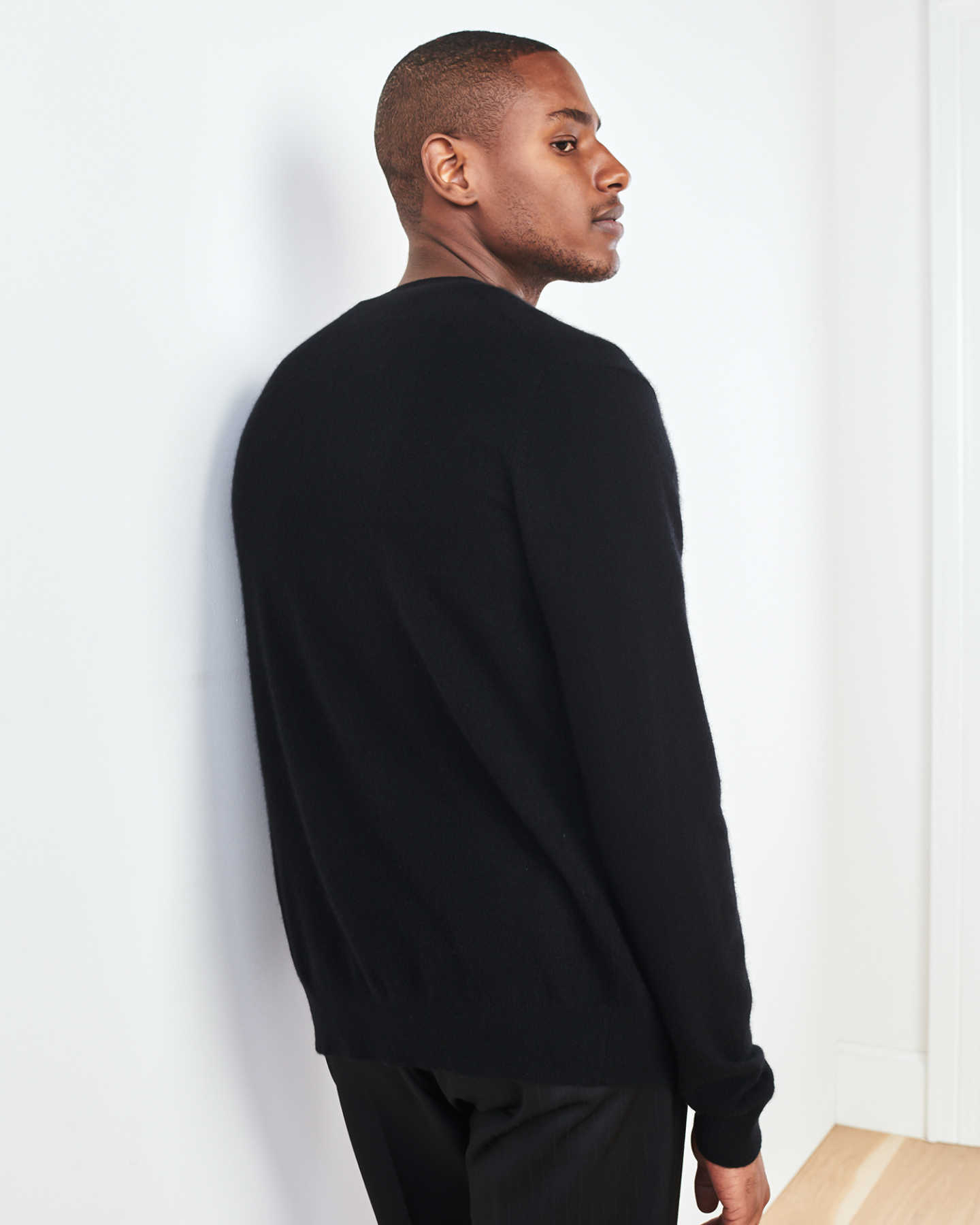 Men's cashmere cardigan sweater in black against wall