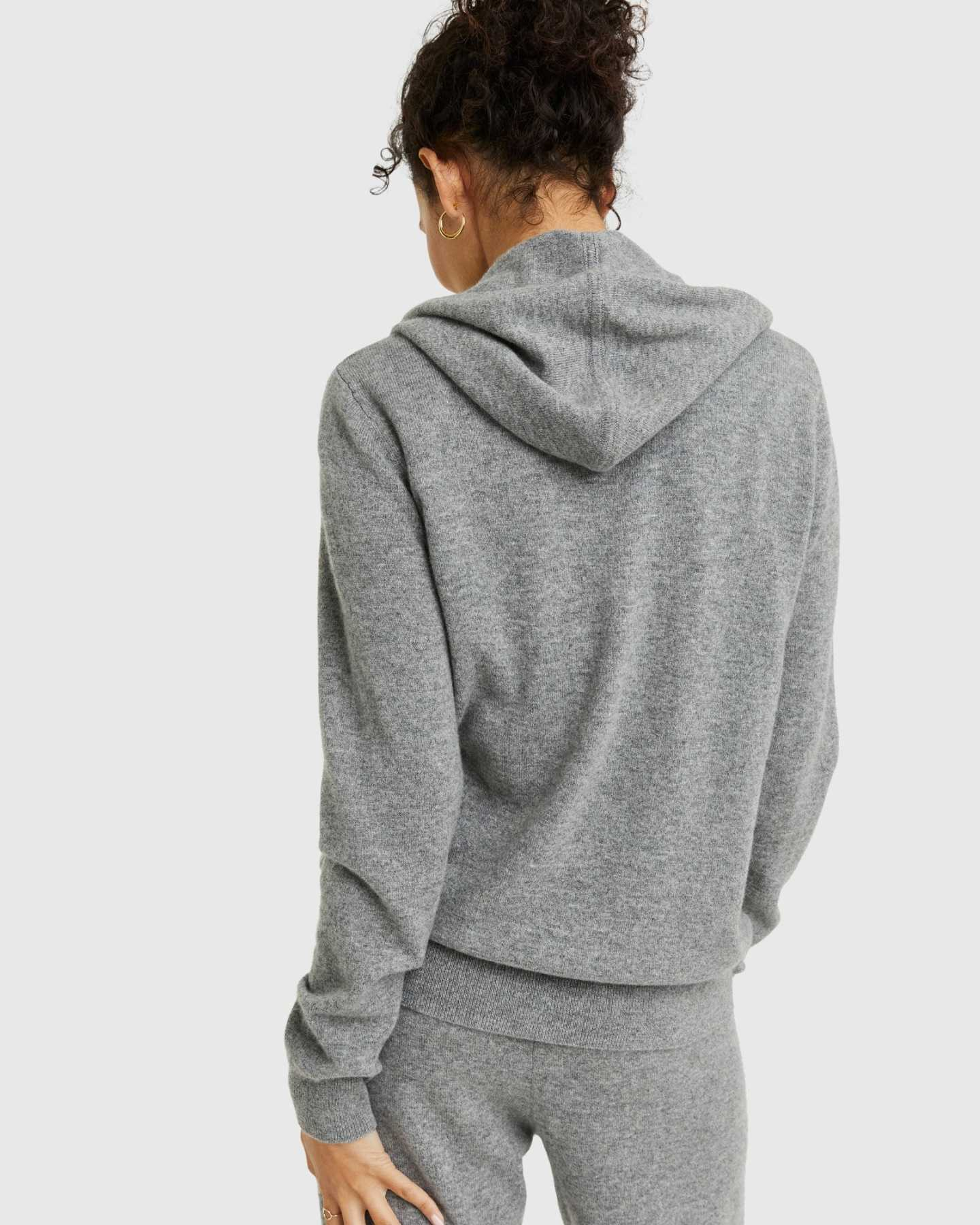 Woman wearing grey cashmere zip hoodie and matching cashmere sweatpants from back