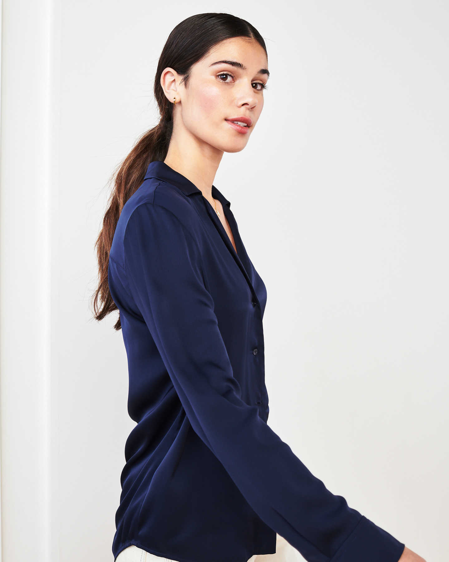 woman wearing silk notch collar blouse in navy walking