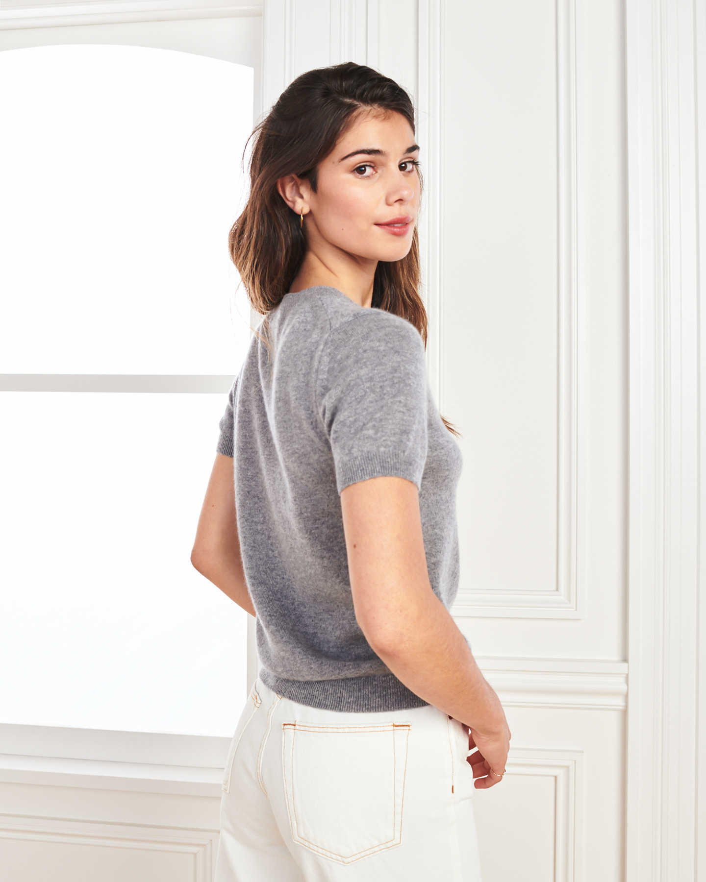woman wearing grey cashmere tee and short sleeve cashmere sweater from back