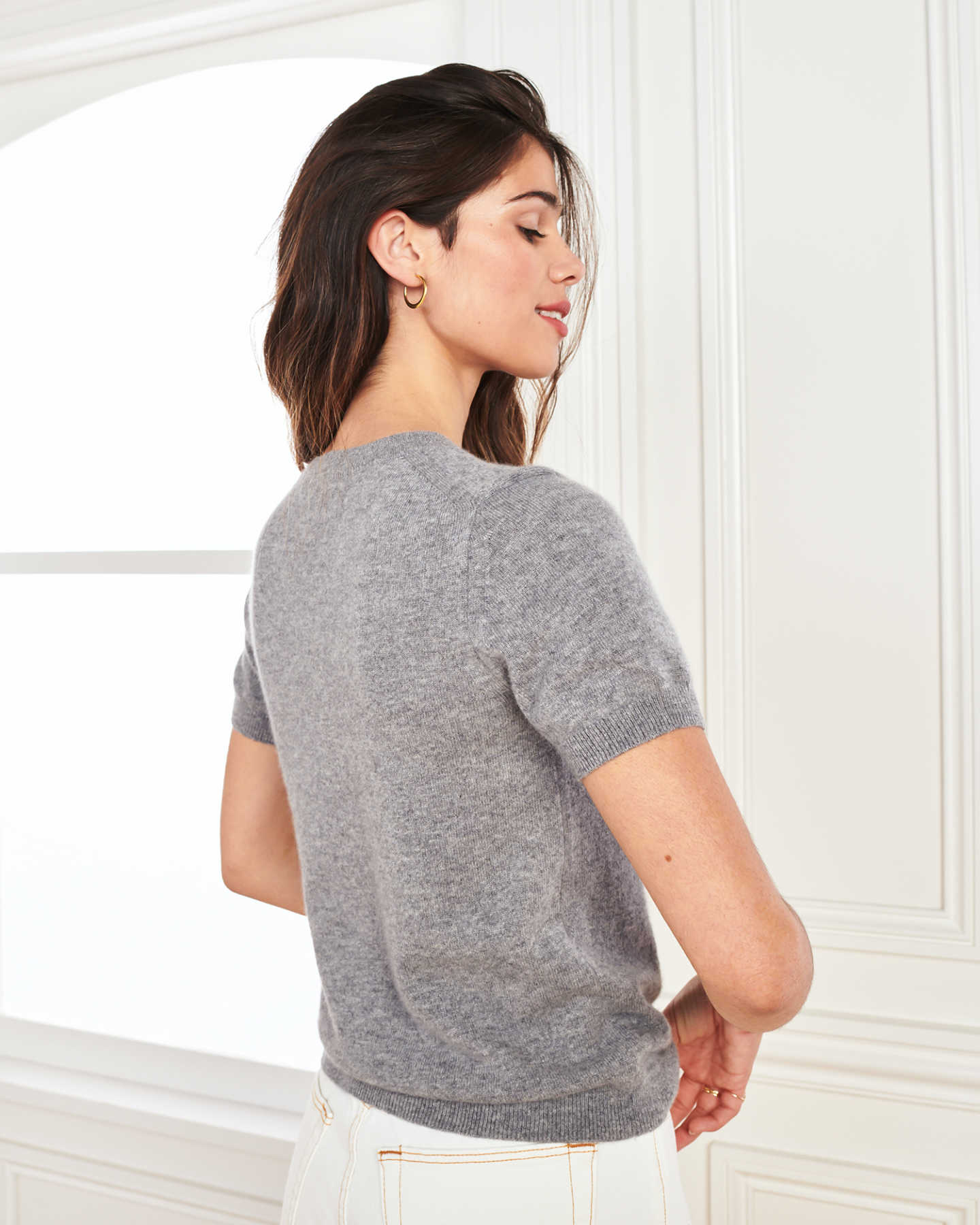 woman wearing grey cashmere tee and short sleeve cashmere sweater from side