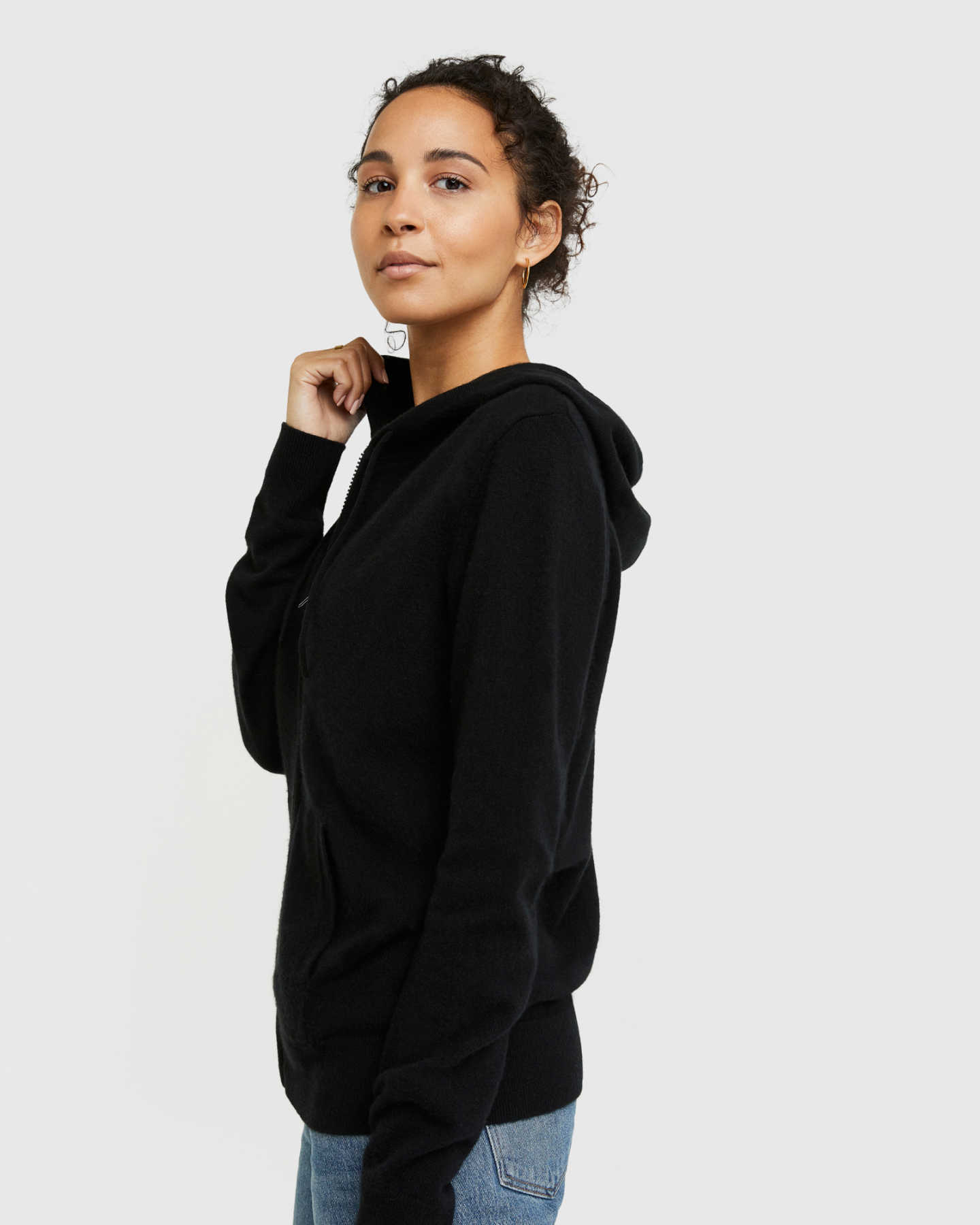 Woman wearing black cashmere zip hoodie and matching cashmere sweatpants from side