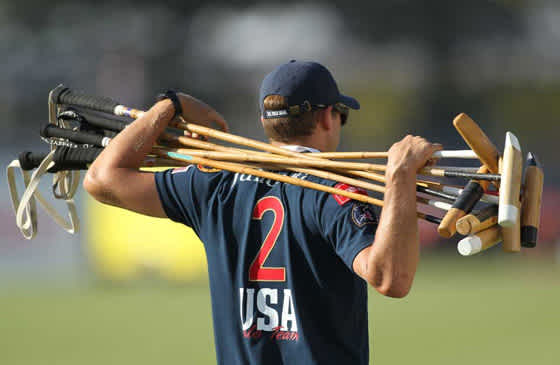 USA polo player holding several polo mallets
