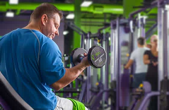 Man lifting weights at YouFit Health Clubs
