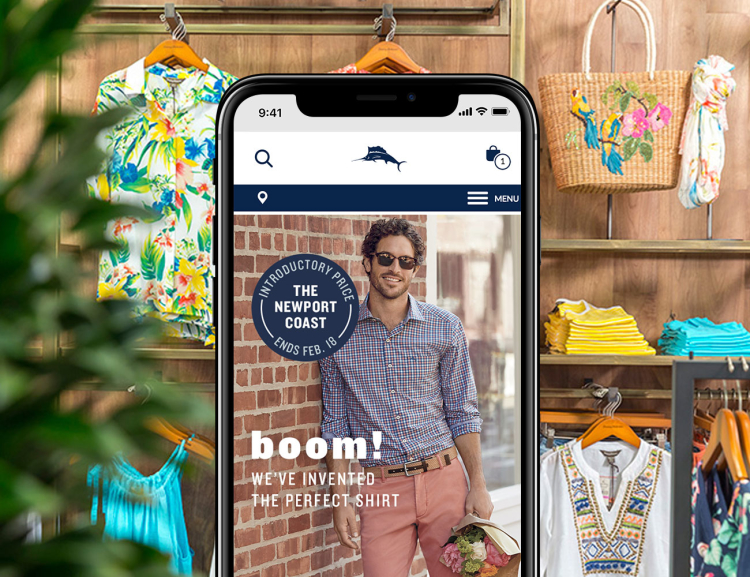 Tommy Bahama website shown on mobile device with Hawaiian shirts, bag and apparel in the background