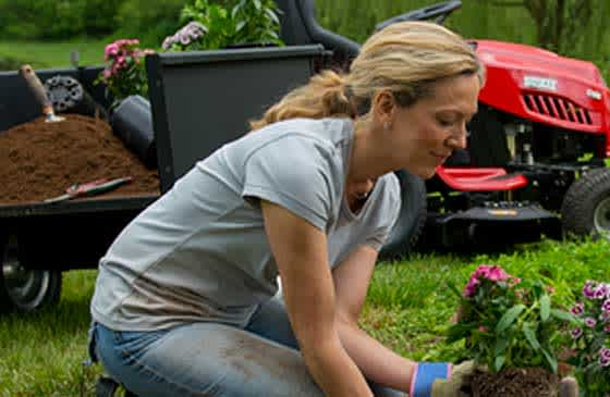 Woman gardening with tractor in background