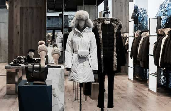 Inside of a Mackage store displaying sorted winter jackets and hats