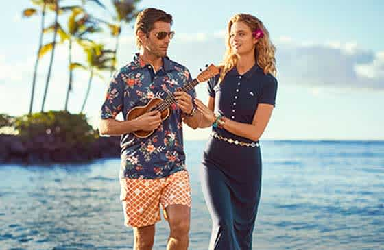 Man playing a ukulele and woman touching his arm standing on an exotic island