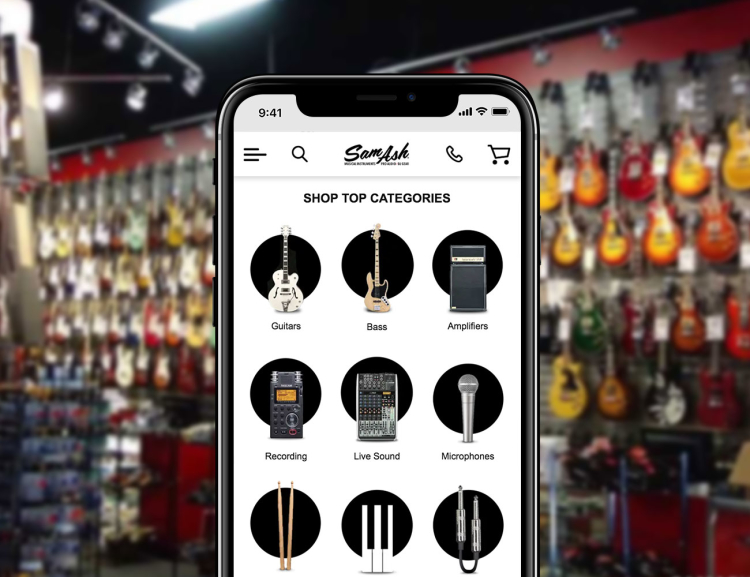 Sam Ash website shown on mobile device with guitar wall in the background