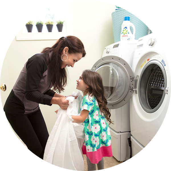 Mother daughter in front of the washing machine