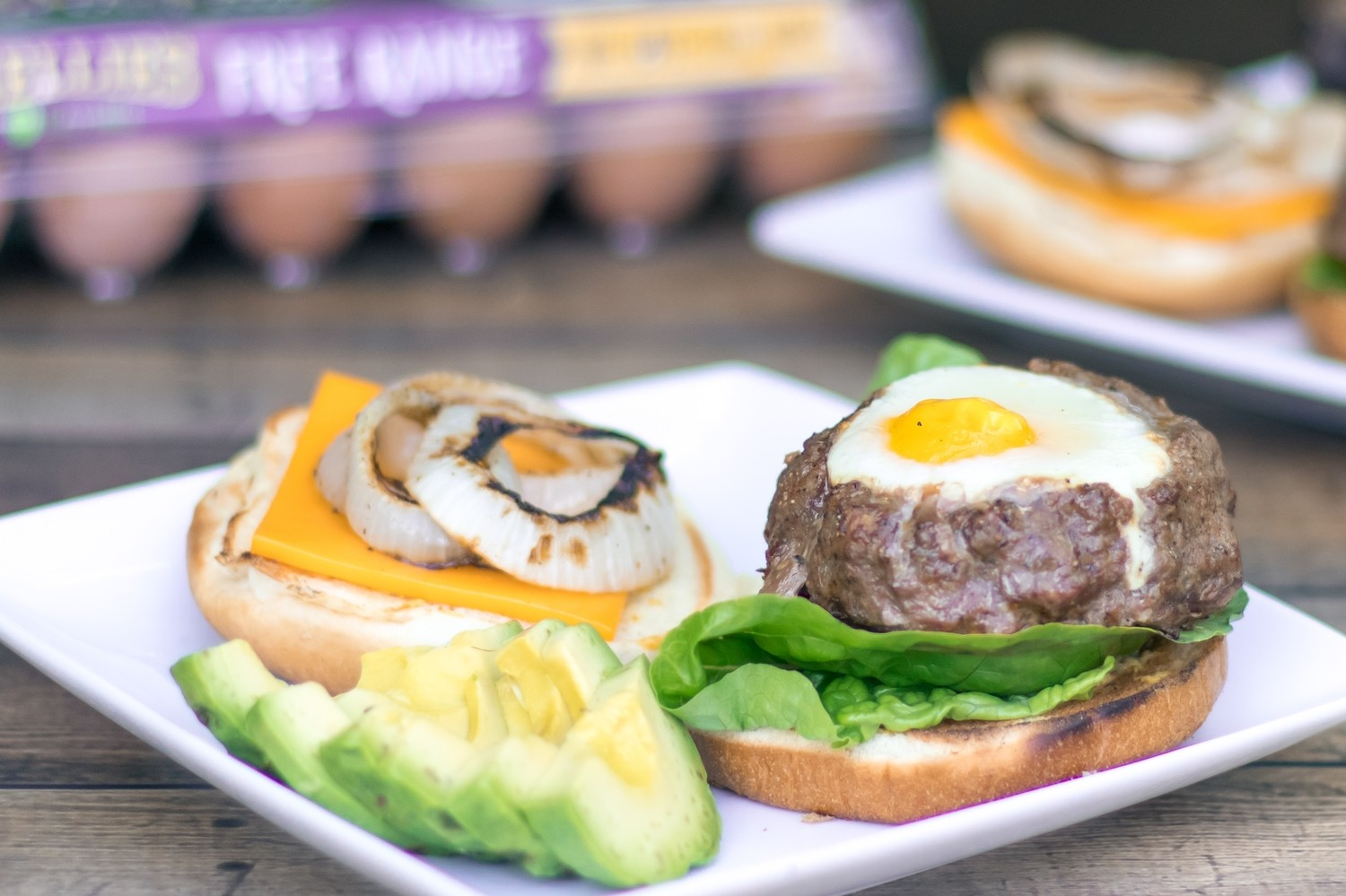 A sunny free range egg cooked on top of a grilled, juicy, seasoned BBQ burger with grilled onions. | nelliesfreerange.com