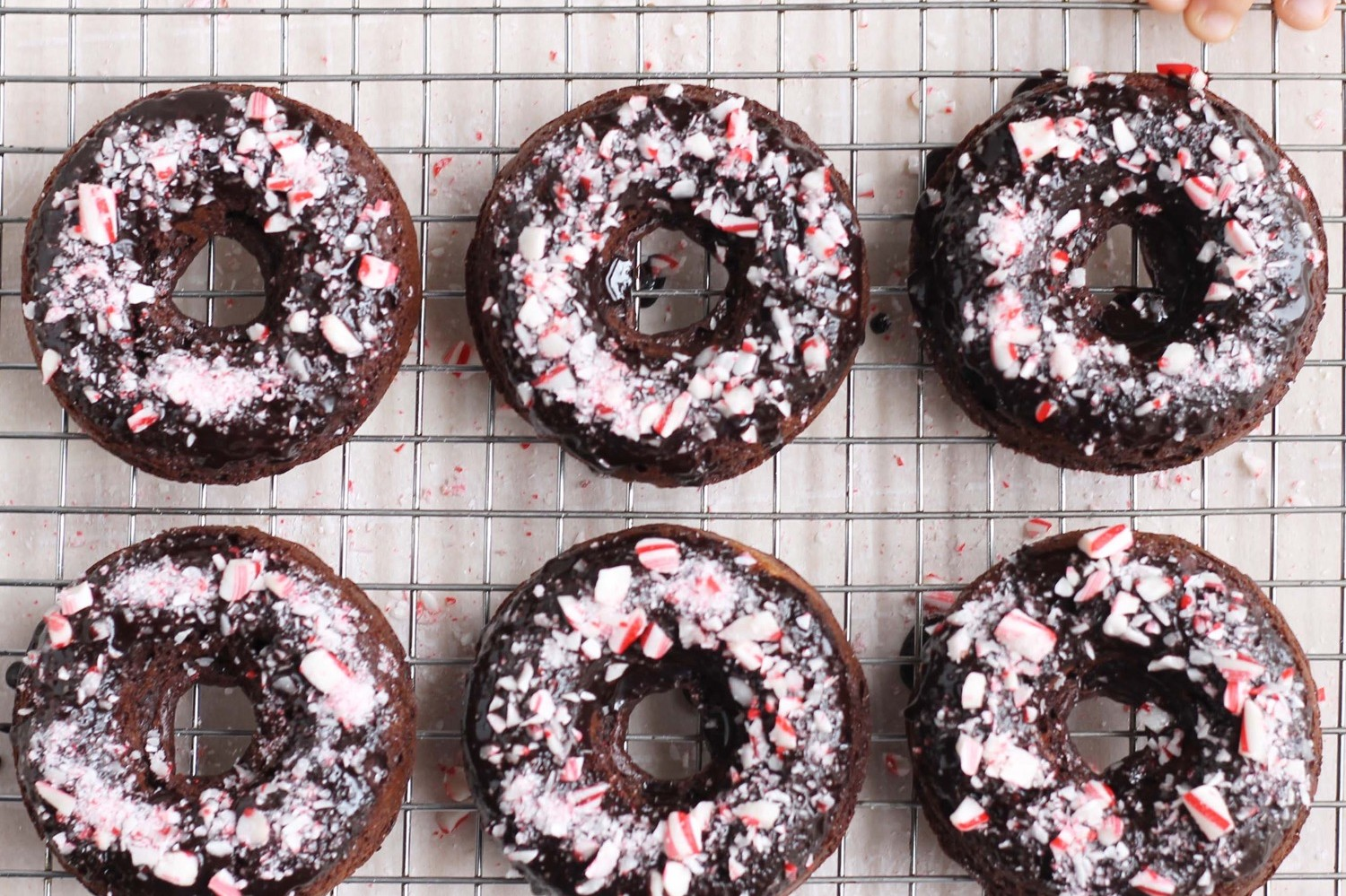 Baked mint chocolate donuts topped with crushed candy canes and naturally sweetened with applesauce and maple syrup. | nelliesfreerange.com