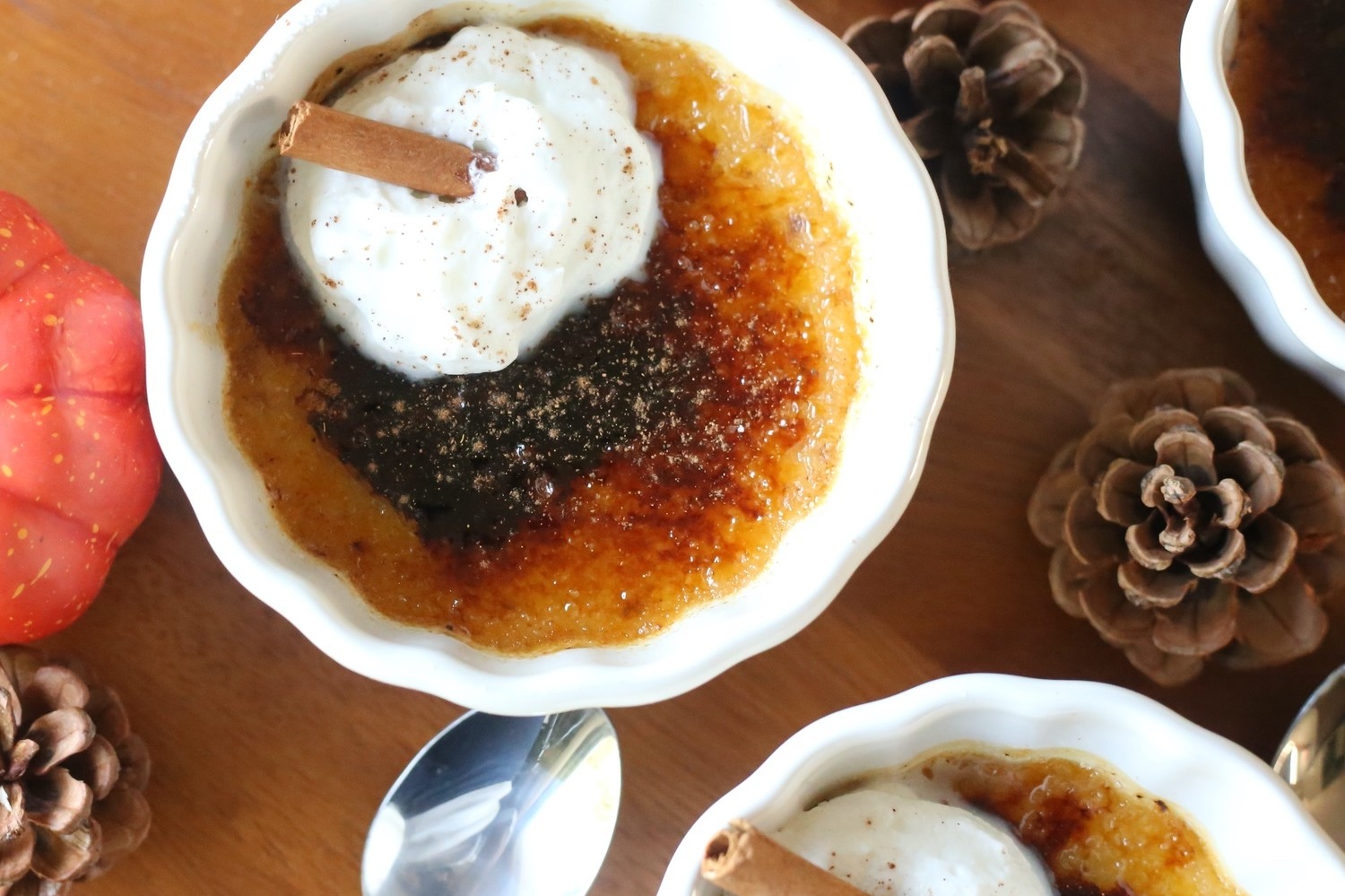 Pumpkin spice crème brûlée with a crackly caramelized sugar crust and rich, creamy pumpkin custard underneath. Topped with a dollop of whipped cream and cinnamon stick for garnish.